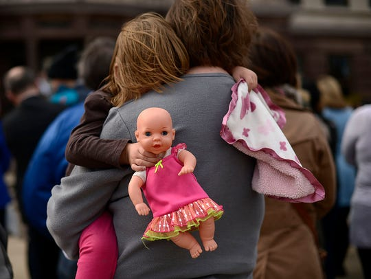 A little girl holds her doll during the Hands around