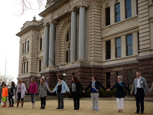 People take part in the Hands around the Courthouse event at the Brown County Courthouse on Wednesday.
