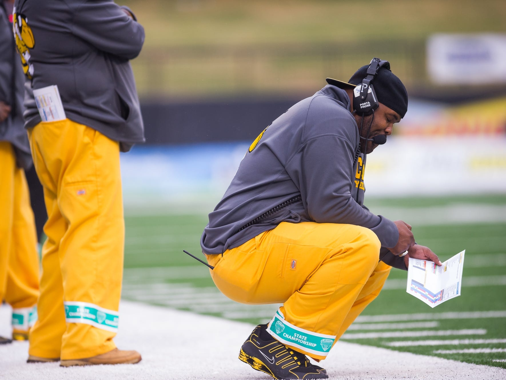 Central High School coach Tyrran Scroggins squats on his sideline during the Yellow Jackets game against Belfry during the KHSAA Commonwealth Gridiron Bowl at Western Kentucky University on Friday, December 5, 2014. Photo by Brian Powers