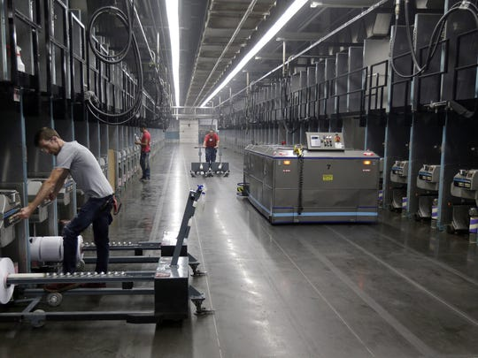 Workers exchange spools of thread as a robot picks up thread made from recycled plastic bottles at the Repreve Bottle Processing Center, part of the Unifi textile company in Yadkinville, N.C.