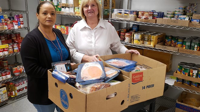Delma Mejia and Capt. Deb Collidge in the food pantry of the Salvation Army in Plymouth.