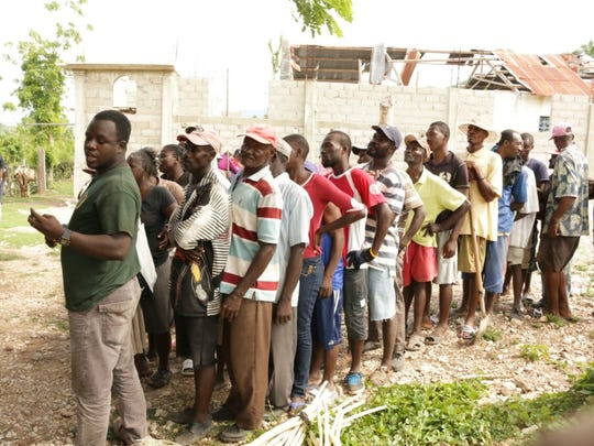 People in Haiti line up to get food. Missionaries of the Heart of Jesus help provide food, medical supplies and other necessities.