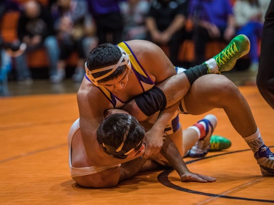 Kirtland Central's Cody Manuelito, top, looks for a pin against Farmington's James Schryver on Saturday at Lillywhite Gym in Aztec.