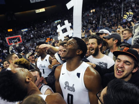 Wolf Pack fans celebrate the 2017 regular-season title with Cameron Oliver. Attendance has been on the rise since Eric Musselman was hired as Nevada's head coach.