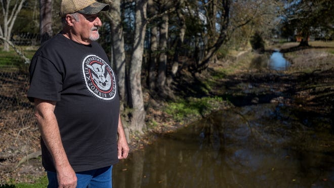 Karl Short stands near a drainage canal bordering his property in Scott, LA, Tuesday, Jan. 27, 2015. Short says blockage in a culvert from leaves and dirt causes frequent flooding on his property.