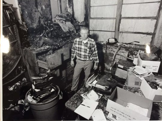 Richard Aulerich, a retired Michigan State University professor, stands in the remains of his office in 1992 after a firebomb attack destroyed 32 years of his research.