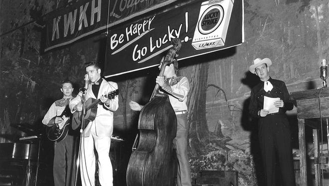 This is the photo of Elvis Presley from his first night on the Louisiana Hayride, October 16, 1954. His musicians were Scotty Moore on guitar and Bill Black on bass. Hayride announcer Frank Page is on the far right.