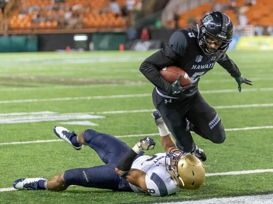 Hawaii wide receiver John Ursua (5) dives over Navy linebacker Elan Nash (8) to score a touchdown in the second half of an NCAA college football game, Saturday, Sept. 1, 2018, in Honolulu. Hawaii beat Navy 59-41. (AP Photo/Eugene Tanner)