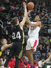 Detroit Edison forward Brian Taylor Jr. scores against Grand Rapids Covenant Christian forward Carson Meulenberg during fourth period action of the Class C MHSAA semifinals Thursday, March 22, 2018 at the Breslin Center in East Lansing, Mich.