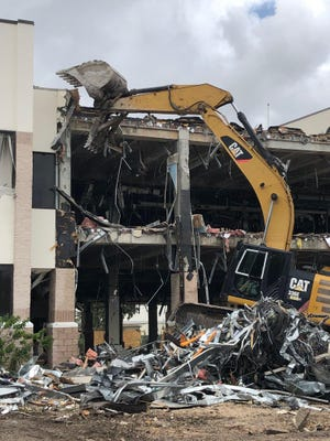 """Demolition, being conducted by BG Demolition, continues on a portion of The Palm Beach Post building complex, Friday, August 23, 2019. The center portion, known as the """"bridge,"""" is being demolished, as part of the new owner's renovation plans for the property."""
