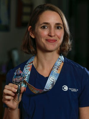 Christiana Care nurse Amy Smythe helped save a Colorado man's life when he collapsed during a half-marathon in Florida. The two connected when he posted a video on Facebook seeking to find and thank his rescuers. Smythe holds her race medal at her Elkton, Md. area home Friday.