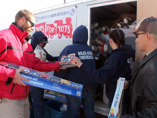 Steffen Milner, from Alamo West, hands Heather Bowlby toys to pack into the Toys for Tots trailer.