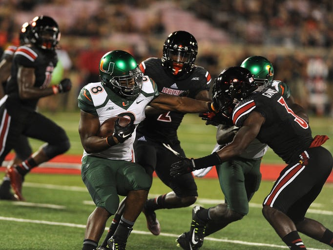 UofL defense corrals Miami running back Duke Johnson in the Cardinals ACC debut on Monday at Papa John's Cardinal Stadium. (By David Lee Hartlage, Special to the C-J) Sept. 1, 2014.