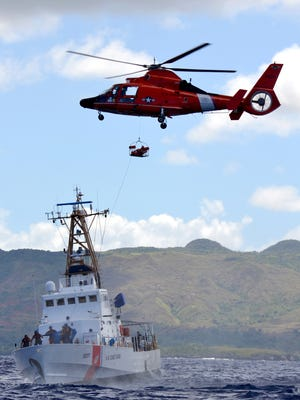 In this March 2012 file photo, an MH-65 Dolphin rescue helicopter crew hovers over the Coast Guard Cutter Washington after receiving word of a critical patient needing immediate air transport during a search and rescue exercise approximately three miles west of Agat Marina. The cutter is in the Federated States of Micronesia to search for two people still missing from an overdue vessel.