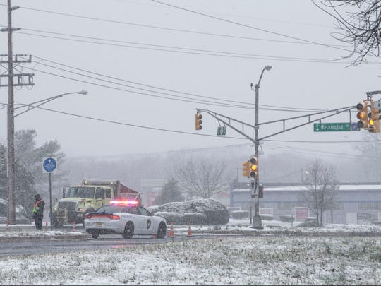 A police officer directs traffic at the intersection of Rt. 37 and Washington Street after a power outage. Snow falls throughout the area as cold air moves in from the north. 