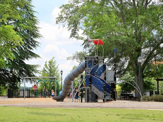 Legacy park features an enclosed toddler area and a wide open fielddotted with shade trees.