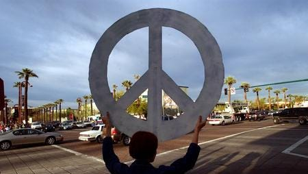 Blue Swadener of Phoenix, holds a giant peace sign Thursday, March 20, 2003, at an intersection in Phoenix during an anti-war protest.