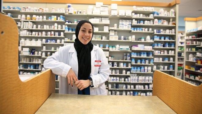 Deena Omar at her job as a pharmacy technician at the CVS Pharmacy on Monroe Avenue in Brighton Monday, Feb. 1, 2016.