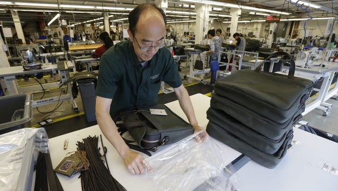 Ying Chau places a completed piece of luggage into a plastic bag at the C.C. Filson Co. manufacturing facility, in Seattle.