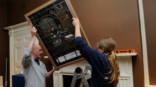 "Chris Miller, left, and Carol Abbott, exhibition installation team, install a stained glass piece Friday at the Decorative Arts Center of Ohio in downtown Lancaster. The new exhibition titled ""A Tradition of Progress"" features decorative arts pieces including glass, ceramic and furniture pieces from the Civil War through World War II. The installation opens Feb. 7 and will be open through May 17."
