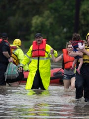 Rescue workers bring out Lana Hauger, 4, right, and