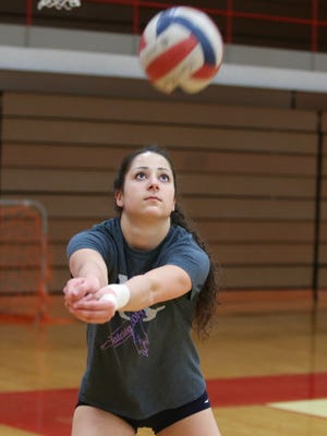 Gia Milana a senior on the Romeo high school volleyball team practices with her team.