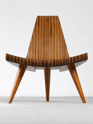 This three-legged chair in five different types of hard wood, with bonded laminated frame and solid, turned joints and legs was designed by Joaquim Tenreiro.