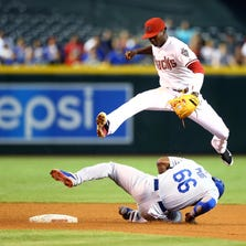 Diamondbacks shortstop Didi Gregorius (top) loses the ball after forcing out Los Angeles Dodgers base runner Yasiel Puig in the first inning at Chase Field on Aug. 26, 2014.
