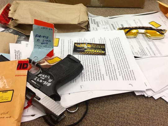 Guns, pricey sunglasses and business cards are among the boxes of evidence laid out in the racketeering trial of David Harris, a member of the Big Money Addicts, on Feb. 16, 2018.