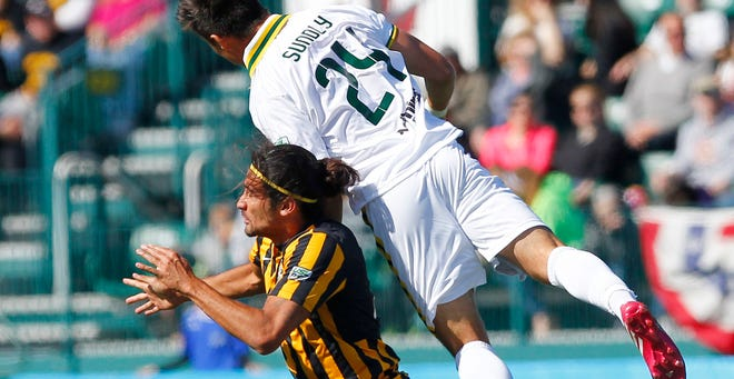 Rochester's Alec Sundly, top, goes over the back of Charleston's Adam Mena for a header during  the Rhinos' home opener on Sunday at Sahlen's  Stadium.