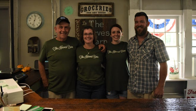 From left to right, Paul and Susie Baumgardener and Sarah and Chad Knox at the Harvest Barn Country Market on Aug. 4. The counter in the picture was made from wood from Paul's barn, which was built in 1914.