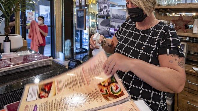 Jennifer Shuman, manager at the Golden Dawn, sanitizes menus.