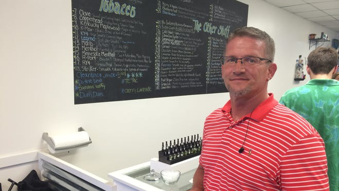 Kelley Page, of Des Moines, stands beside the counter in Great Alternatives E-Cigs shop.