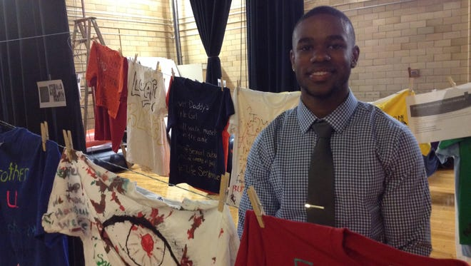 Dre Johnson poses with some of the shirts from the Clothesline Project at LyncX Academy.