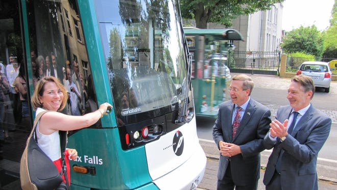 Cindy Huether helps christen a new street car with sparkling wine in Potsdam, Germany, as mayors Mike Huether and Jann Jakobs applaud the tram named for Sioux Falls.