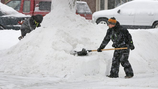 Danny Lee, right, shovels snow while his son Kyle, 9, works on moving a big pile of snow near his N. 25th Street driveway Saturday December 17, 2016 in Sheboygan.