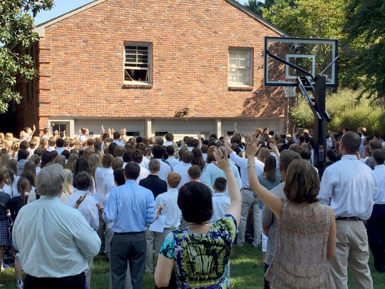 More than 400 students and teachers gather on Sept. 6, 2016 in the driveway of Christ Presbyterian Academy teacher Ben Ellis, who has terminal cancer, to support with hymns and prayers.