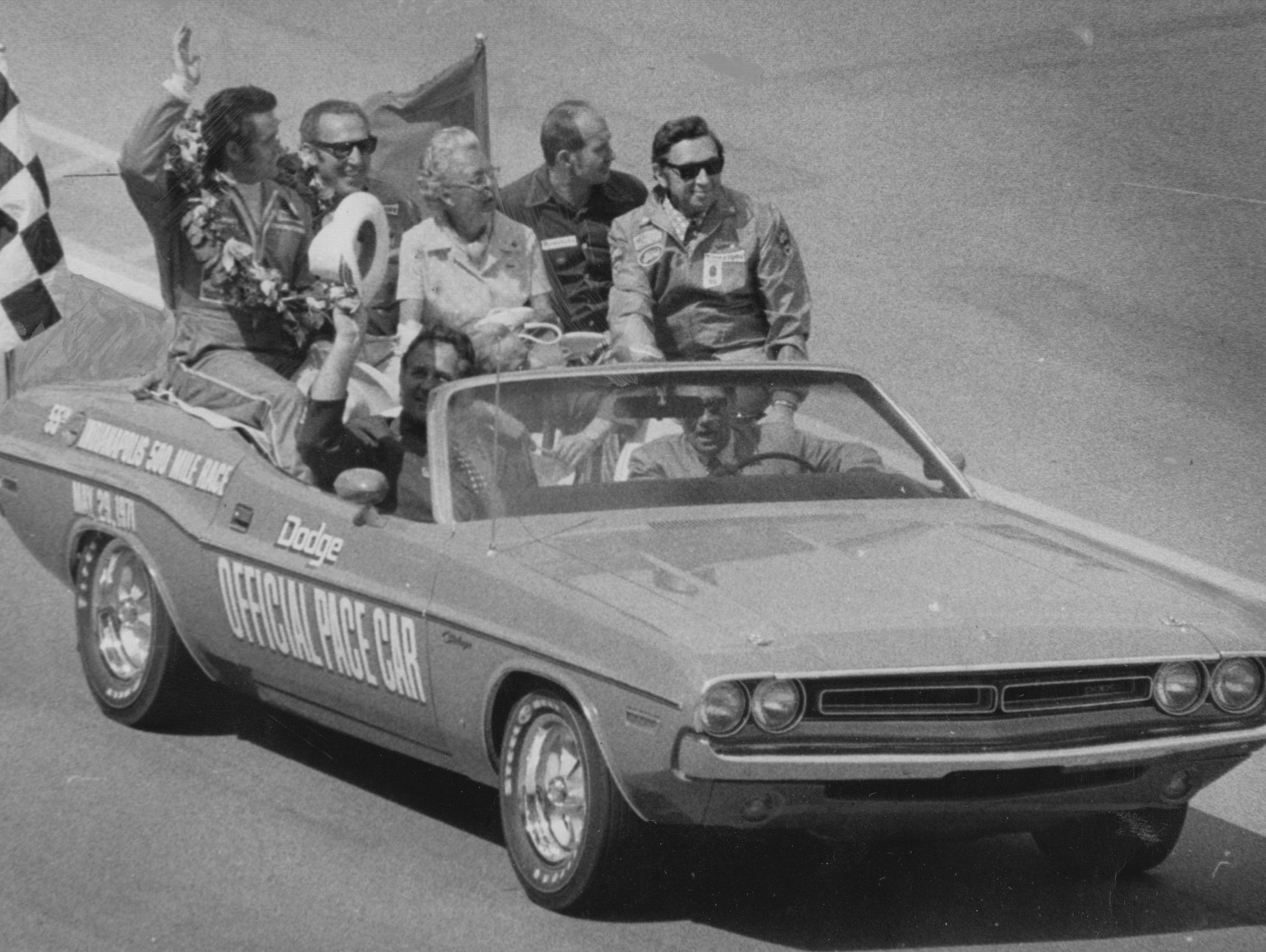 "Al Unser waves in the victory parade beside mechanic George Bignotti, ""Mom"" Unser and Parnelli Jones."