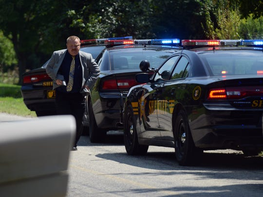 Fairfield County Sheriff's Office Det. Andy Robberts runs back to his vehicle as deputies talk to a suspect Thursday, Sept. 3, 2014, in the 1700 block of Old Rushville Road NE in Rushcreek Township.