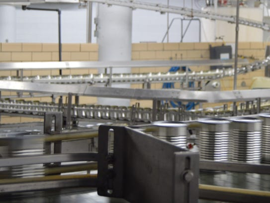 Cans of chicken broth zip along the production line