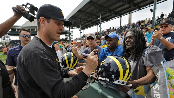 Michigan football coach Jim Harbaugh signs autographs before a spring training baseball game between the Pittsburgh Pirates and the Detroit Tigers on Wednesday, March 2, 2016, in Bradenton, Fla.
