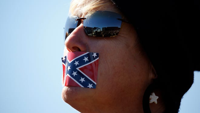 Sunglasses reflect the audience as a protester wears a Confederate battle flag sticker on her mouth as part of a silent protest to the current Mississippi state flag during the grand opening ceremony for the Museum of Mississippi History and the Mississippi Civil Rights Museum on Saturday in Jackson. A small group of protesters wore the stickers and stood silently holding an alternative flag during the program.