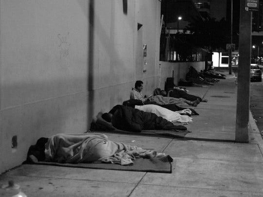 Homeless persons sleep on the sidewalk.