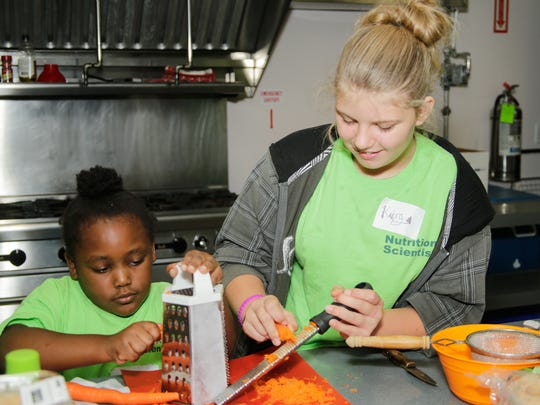 Hope for Families Center children Ashlee and Kiera learn to grate carrots during a Growing Healthy Kids session in fall 2017.