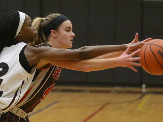 Edison's Djeynaba Thiam, left, and East Rochester's Maddy Walsh, right, fight for a inbounds pass.