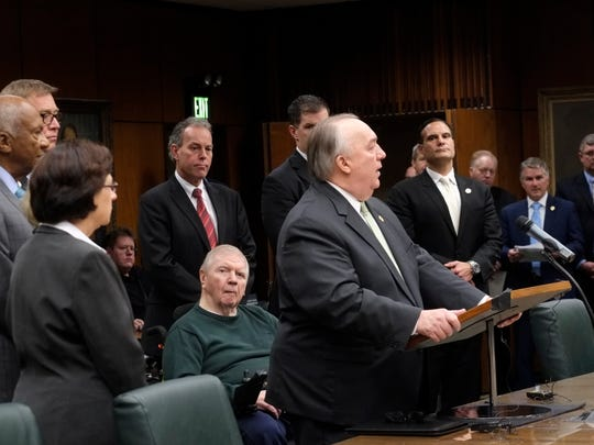 With the MSU Board of Trustees at his side, former Michigan governor John Engler makes a statement at the Trustees meeting Wedneday, Jan. 31, 2018 in East Lansing, Michigan. John Truscott, Engler's former press aide in the governor's office, is seen two people to the right of Engler in the blue tie.