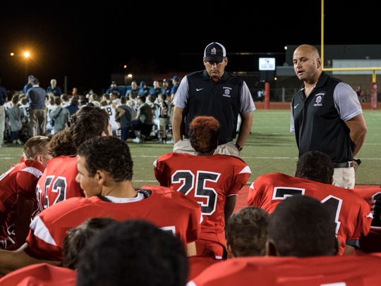 Harrison Head Coach Lane Oxley talks to his team after
