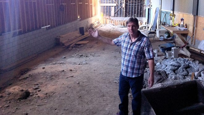Nigel Chisholm, owner of The Village Jester, shows the condition of the Ojai Playhouse in 2015, a year after a water main break flooded the business.