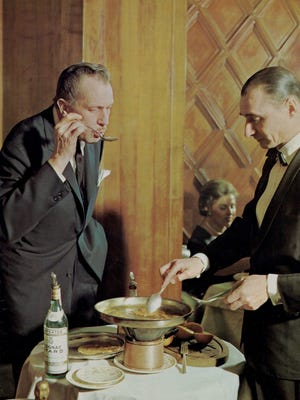Vincent Price, actor and food connoisseur, taste-tests a dish at one of many culinary events he hosted for friends.