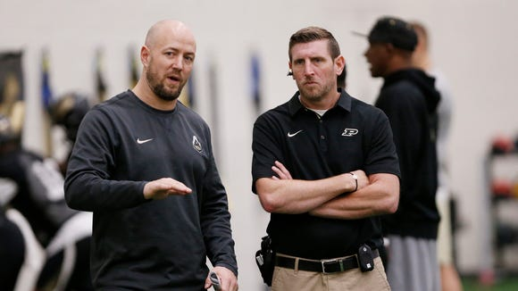 Justin Lovett, left, director of football strength and conditioning, talks with Ryan Collins, associate director of sports medicine, as they watch players during Purdue spring football practice Friday, March 30, 2018, inside the Mollenkopf Athletic Center.
